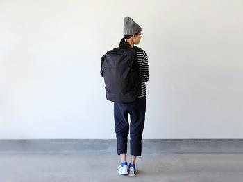 白黒ボーダーのトップスに、デニムパンツとビッグサイズのリュックを合わせた着こなし。ベレー帽やスニーカーを合わせて、カジュアルにまとめています。