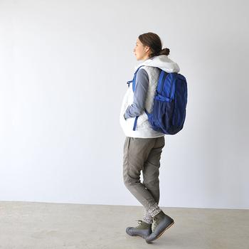 青色のアウトドアリュックに、白のダウンベストやカーキのパンツを合わせたコーデ。足元は黒のブーツと靴下コーデで、メンズライクでカジュアルな大人の着こなしに。