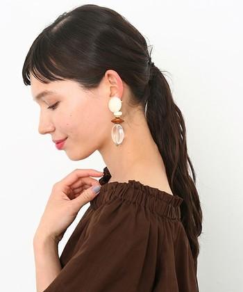髪を後ろでタイトに束ねて、レトロな大振りのイアリングを引き立たせています。アイホールにブラウンのアイシャドウを強めにのせて、大人シックな印象に。