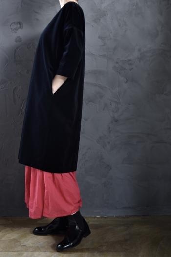 ちょっぴり華やかさが欲しいときは、鮮やかなレッドのスカートを仕込んで。ワンピースの裾から、さり気ない女性らしさがこぼれます。