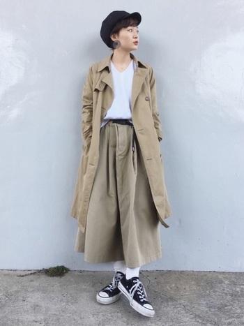 ベージュのロングスカートとトレンチコートのワントーンコーディネート。黒の帽子とスカートのベルト、スニーカーが引き締めポイントに。