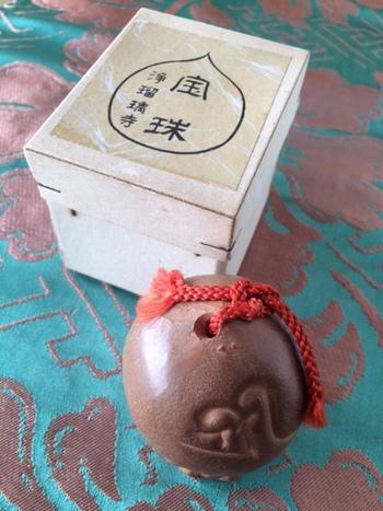 """浄瑠璃寺(京都)の宝珠土鈴・・・桃のような形。彩色もなく簡素な土の素焼き。裏には浄瑠璃寺の刻印があり、表には吉祥天を意味する梵字(ぼんじ)が描かれています。""""宝珠""""とは、仏像の持ち物を模したもので、この珠はあらゆる願いを叶えてくれるありがたいお守り。まさにラッキーアイテムですね!"""