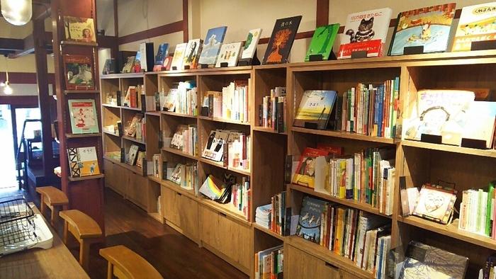 京都市北区・大宮商店街の一角にある、町家を改装した京都ならではの赴きある佇まい。京都で書店や雑貨店を手がけている「ふたば書房」直営の絵本カフェです。  「ふたば書房」社長は絵本専門士。その社長が直々にセレクトしたお墨付きの国内外の絵本、600タイトルほどが揃います。小上がりスペースには自慢の絵本がずらり!