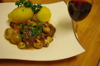 """『ブフ・ブルギニョン』は、⽜⾁を⾚ワインで煮込んでつくる、シチューのような料理。「ブフ(boeuf)」とはフランス語で""""⽜⾁""""、「ブルギニョン(Bourguignon)」とは""""ブルゴーニュの""""という意味を指します。 元々はブルゴーニュ地方の貧しい農⺠たちが、筋の多い牛肉をなんとかして食べるため、飲み残しのワインで煮込んでつくったものなんだそう。そのようなエコ料理感覚のものですが、ビーフシチューの原型になったとの説もあります。ブルゴーニュ地⽅では各家庭ごとにオリジナルレシピがあるそうですよ。"""