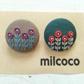 ひと針ひと針縫われたお花模様のくるみボタンのブローチ。とてもナチュラルでロマンティックなデザインです。