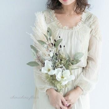 束ねた花の茎を持つタイプのクラッチブーケは、摘んできた花々をそのままブーケにしたようなカジュアルな雰囲気。クラシックなAラインからエレガントなマーメイドラインまで、幅広いドレスに似合うブーケです。