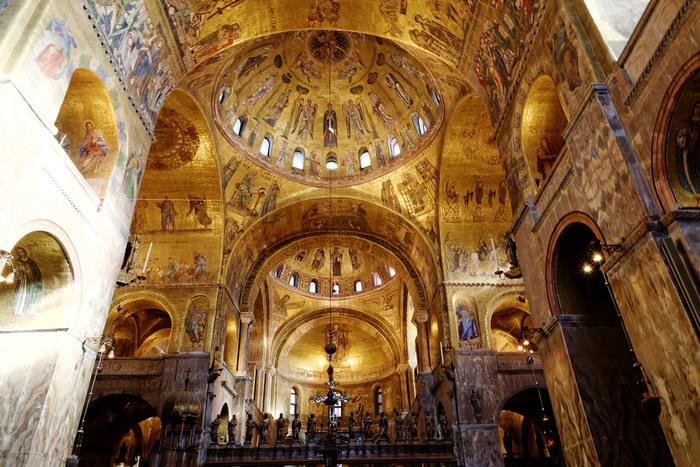 サン・マルコ寺院内部の豪華さは、思わず息を呑むほどです。金とガラスモザイクの装飾が施されたドーム状の天井と壁は、黄金色に輝いており、ヴェネツィア共和国が歩んできた煌びやかな歴史を物語っているかのようです。