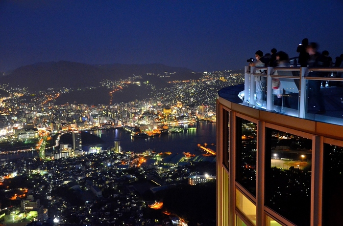 """長崎の夜景の名所として有名な「稲佐山」。山頂の展望台からは、昼は雲仙や五島列島まで一望でき、夜もまた絶景!「夜景サミット2012 in 長崎」で世界新三大夜景にも認定され、その美しさは""""1,000万ドルの夜景""""と評されるほど。"""