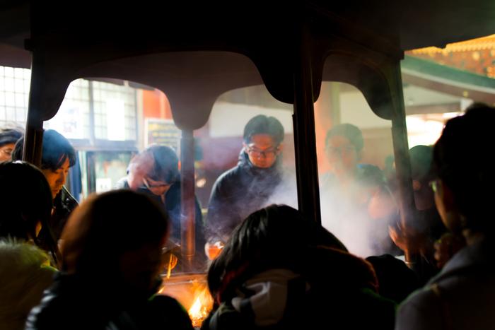 常香炉(じょうこうろ)でお線香の煙を浴びる参拝客たち。お線香の煙を浴びることは、邪気をはらい、身をきよめるという意味をもつとされています。