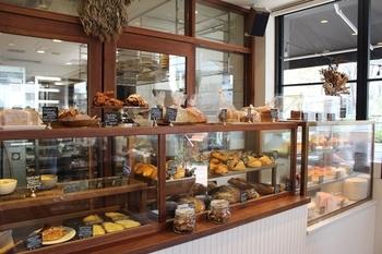 白いタイルとウッディなインテリアが明るく、清潔感のある店内。ショーケースには焼きたてのパンがずらりと並んでいます。