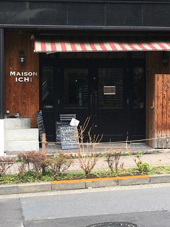 代官山駅の正面口から歩いて2~3分、交番前の交差点にあるパン屋さんが「MAISON ICHI (メゾン・イチ)」。本格的なフランスデリとパンが人気のお店です。黒いドアと赤白のストライプのひさしが目印です。