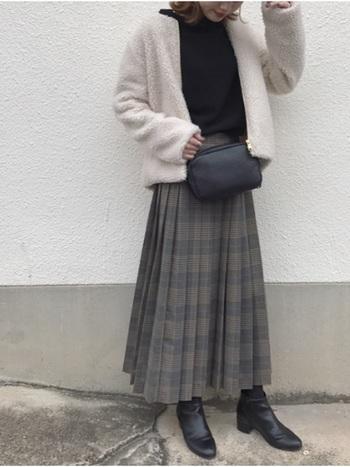 チェックのプリーツスカートは今年のトレンドアイテムのひとつ。アウターがカジュアルでも、足元がショートブーツだと、少しシックな雰囲気に。