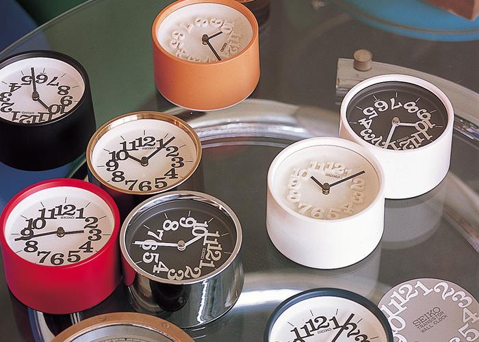凸状のアラビア数字がぎゅっと詰まって浮かび上がっている、なんとも可愛らしい文字板は、名デザイナー・渡辺力さんがデザインし、1971年に発売された『小さな壁時計』がモチーフになっています。当時、華美な装飾を施した大型の掛け時計が主流だったなかで、小さくてシンプルなデザインは画期的だったそう。50年近く経った今でも色褪せない魅力は、いかに洗練されたデザインであるかを証明しています。 『Riki』は渡辺力さんの遺したデザインをベースにした腕時計シリーズとして、シンプルでモダンなファッションを好む男女ともに幅広い世代から支持されています。