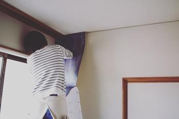 壁紙は少し大きめに切っておき、上下に余裕をもたせた状態で垂直に貼り付けます。画鋲で仮止めをして作業を行うとスムーズです。