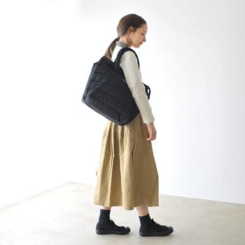黒色のキルティング素材を利用したトートバッグは「marimekko(マリメッコ)」のもの。カーディガン×シャツ×チノスカートのナチュラルガーリースタイルに、黒色の大きめトートとシューズでふわっとした印象をキュッと引き締め。