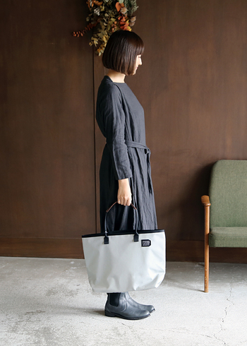 ワンピース&ブーツのブラックコーデに、薄いグレーの大きめトートを合わせたモノトーンコーデ。白だと色合いの差がはっきり出過ぎてしまうので、あえてグレーを選ぶことで大人っぽい雰囲気を演出しています。