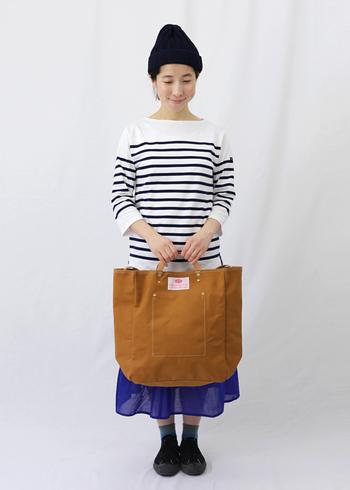 茶色の大きめトートバッグに、ボーダーのトップスと青色のスカートを合わせた着こなし。ボーイズライクな印象のカラーリングですが、ボトムスをスカートにすることで女性らしさもしっかり残したカジュアルコーデに仕上げています。