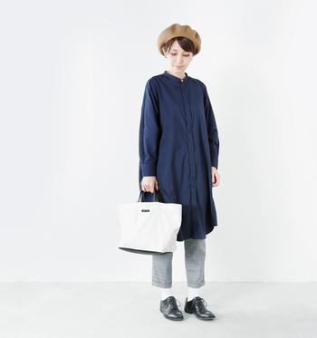 ネイビーのシャツワンピースに、グレーチェックのパンツやベレー帽というマニッシュスタイル。白色のトートバッグを合わせることで、ダークトーンのコーデに爽やかさと女性らしさをプラスしています。