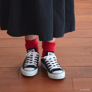 黒色のスニーカーに、赤色の靴下を合わせたコーデ。黒や白のスニーカーなら、赤・青・緑などの原色系カラーを合わせるとおしゃれな印象に仕上がります。長めの靴下なら、ゆるっとたるませるのも可愛い♪