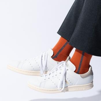 白色のスニーカーに、オレンジのデザイン靴下を合わせたスタイルです。真っ白のスニーカーなら。どんな靴下を合わせても浮くことはありません。少し奇抜なデザインやカラーのものを選んで、黒やネイビーなどのベーシックカラ―ボトムスと合わせましょう。