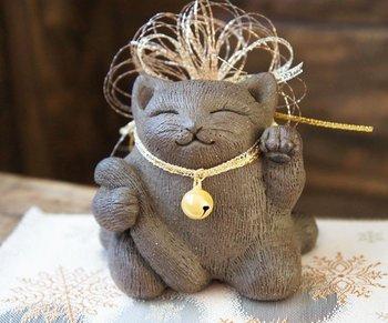 「黒猫の招き猫土鈴」・・・優しい表情で左手を上げている黒猫の招き猫の土鈴です。細かい毛流れの線彫りも肉球もしっかり表現しています!