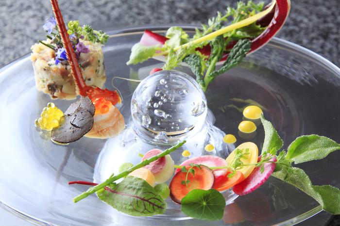 お食事は、フレンチレストランでの本格コース。獲れたての活魚をはじめ、和牛、伊豆鹿、花野菜などの食材は、近隣で育てられた地元のものを使用。熱海のご馳走が勢ぞろいします。季節感を大切にした盛り付けは、芸術的な美しさでうっとりしますね。