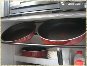 キッチンのガスコンロ下収納でも、突っ張り棒が大活躍。ティファールなどの重ねられるフライパンは、下の方に重ねた物を取り出すのが億劫ですよね。このように突っ張り棒2本のうち手前側を少し低めにセットすると、フライパンを重ねずに収納できて取り出すのも片付けるのも楽々です。