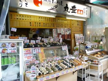 """築地場外市場の端っこに店舗を構える""""丸豊""""は、築地で働く方々に大人気のお店。朝早くから、おにぎりを求めて多くの人々が訪れるそう。"""