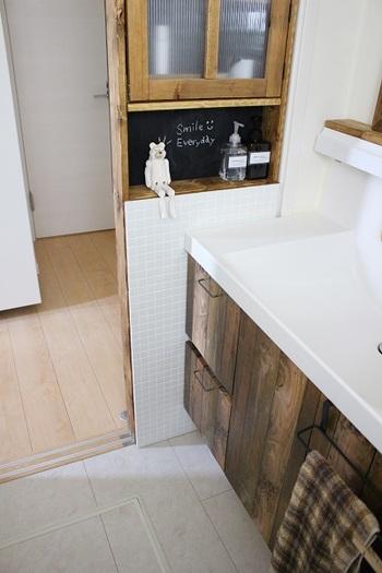 洗面台の下の扉に落ち着きのある木のリメイクシートを貼りつけて。取っ手もアイアン風のものにチェンジして、全体的な雰囲気を統一しています。