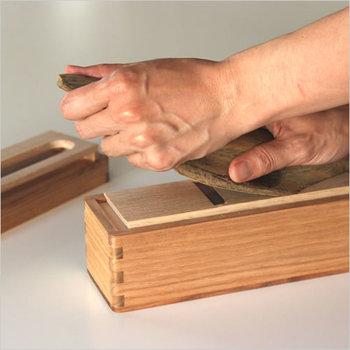 """ambai(あんばい)=塩梅。日本らしい言葉です。""""日本のものづくり""""をテーマに活動するインテリアデザイナーの小泉誠氏が手がける道具シリーズの名です。作り手とデザイナーが組み、使い手にとっていい塩梅のものをつくりだす。その作品のひとつがこの鰹箱(かつお節削り器)。"""