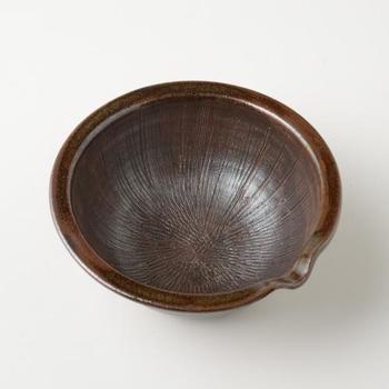 """鹿児島県にある焼き物工房""""野はら屋""""。沖縄の読谷山焼、北窯で修業をした鹿児島出身の佐々木かおりさんの工房。  野はら屋の作品は沖縄の形を感じさせながらも鹿児島の伝統を伝えてくる。そして、このすり鉢。""""薩摩の黒""""といわれる黒釉薬の鉢は、他の道具の間においてもよくなじむ。  女性の手によるものと思えないほどの力強さもあり、器としても食卓に迎えたくなる存在感です。"""