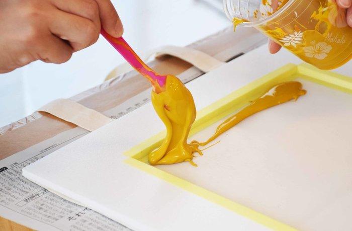 版の作り方をざっくり説明いたしますと、まず、白黒で書かれた原画(または写真)を、感光乳剤を塗布した版に置いて感光させます。感光乳剤は光(紫外線)で硬化するので、転写された原稿の「白」の部分は固まり、「黒」の部分は水で流すとメッシュの穴が通るようになります。このメッシュの穴からインクを通して印刷する、という方法です。(写真参照)