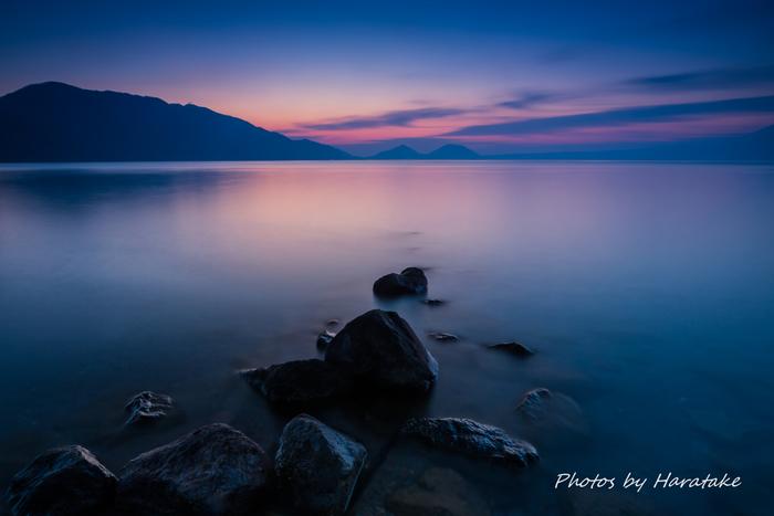 札幌から1時間ほどの千歳市にある支笏湖は、天候や時間帯、季節によってさまざまな表情を見せてくれる幻想的な湖です。夜明けには、空と湖面に美しいグラデーションが広がります。