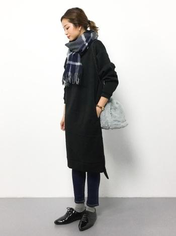 黒のニットワンピース×濃紺デニムを組み合わせたシックな配色コーデ。チェック柄マフラー&マニッシュシューズで、シンプルな装いにクラシカルな雰囲気をプラス。ダークトーンでまとめたクールな着こなしに、フェミニンなファーバッグをアクセントに効かせることで、全体の印象がカチッとし過ぎず大人可愛い印象になります。