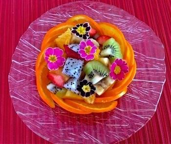 フルーツの切り方と盛り付け方を工夫した、簡単でおしゃれなフルーツバスケット。角切りにしたフルーツやエディブルフラワーを器に入れたら、薄くスライスして半円に切ったオレンジで囲みます。花や果実摘みのカゴのようで可愛いらしい♪
