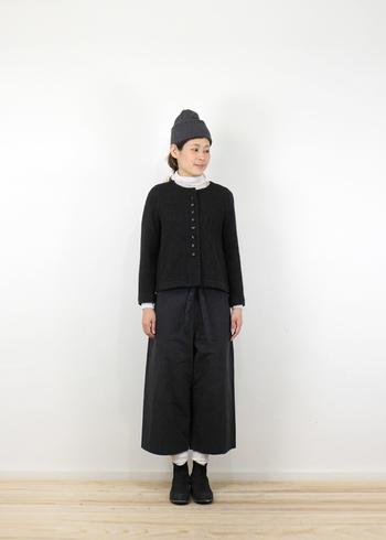 黒のカーディガンに、白のタートルネックをインした着こなし。靴下も白色で合わせて、黒コーデの中にメリハリを利かせています。