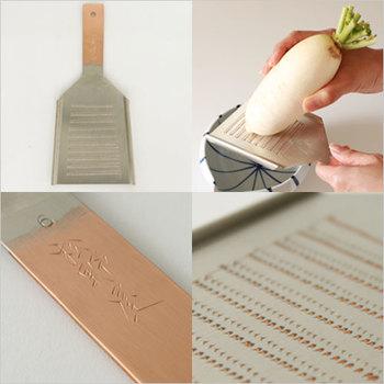 """特徴は銅でできたおろし金の部分。大阪の職人が熟練した技で、きれいに素材をおろせる微妙な刃ならびになるように仕上げています。ひとつひとつ、手打ちで起こしたこの刃の凄さ、ぜひ使ってみてほしい。  持ち手の部分に刻印された""""松野屋""""の文字にも品格が表れています。薬味などをおろすのに役立つミニサイズ、通常のおろしに便利な六型。お値段もそれなりですが、その価値がある逸品です。"""