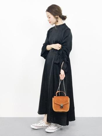 黒ワンピースに、茶色のバッグと白スニーカーで色をプラス。バッグや靴を変えるだけで、黒ワンピースの印象も大きく変わりますね。