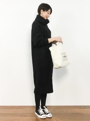 黒のタートルネックワンピースに、黒のタイツとスニーカー。バッグとシューズに少し入った白色が、黒コーデを大人上品な印象にまとめています。