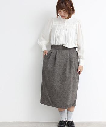 ギャザーが入ったスタンドカラーのブラウスには、正統派スカートをセットしてクラシックなスタイルに。腰回りをふわっと包むタックが、コーディネートに女性らしさを匂わせます。