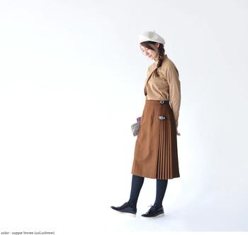 """細かなプリーツが施されたベルトつきスカートは、誰の目にも好印象に映る王道アイテム。ベージュ系のトーンでまとめ、色使いでも""""たおやかさ""""を表現して。"""