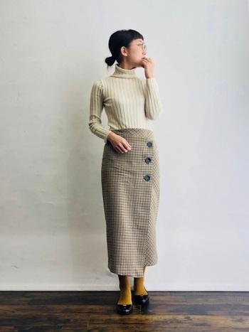 細かいチェック模様と、大きめの三つボタンがモダンなラップスカート。徐々にタイトなラインを描くペンシルシルエットであれば、嫌味のない色香をふんわりと醸せます。