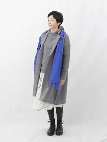 ふんわり揺れる薄手のフレアスカート。その軽さを損なわないよう、ニットとコートには明るめのグレーを指名します。