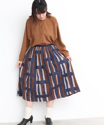 スカートとカーディガンを、ライトブラウンでカラーリンク。着こなしに統一感が生まれ、ユニークな柄スカートも大人シックに傾きます。