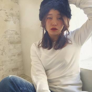 ぬくぬく素材の帽子で、2つ結びを冬らしくアレンジ。帽子を被った後は、前髪や顔回りの髪をバランスよく整えましょう。