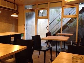 階段をおりると木のぬくもりを感じるやわらかな印象のカフェ空間が広がります。二人掛けのテーブルと大きめテーブルが設えられ、朝から満席になることもしばしばという人気店です。