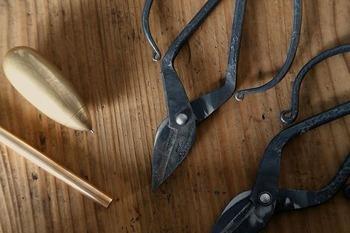 """使い続ける、作り続けるなかで生まれたエピソードと文具展。手作業で生み出される「TAjiKA」の鋏(右)や""""素材の力""""をキーワードに作られる文具ブランド「MUCU」の真鍮・青銅のペン(左)などをご紹介。よい風合いに経年変化した実物も見ることができます。"""