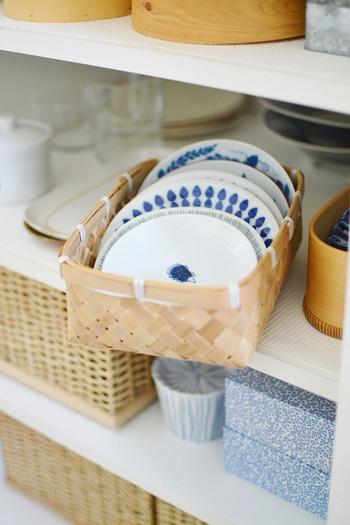 浅い段にはカゴを入れて引き出せるようにすると、奥の食器もスムーズに取り出せるようになります。よく使う取り皿サイズのプレートはこのまま、さっと食卓に出すこともできて便利です。