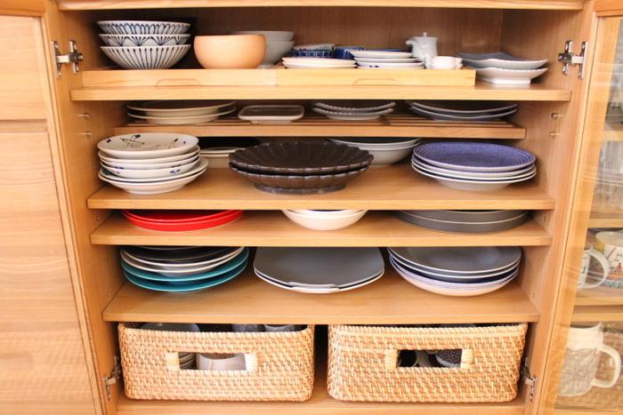 大きめプレートは種類ごとに分けて、せまい段にも美しく収められています。取り出しにくい一番下の段にはラタンバスケットを入れて、引き出しにするという工夫が。木製食器棚にラタンバスケットはよく合いますね。