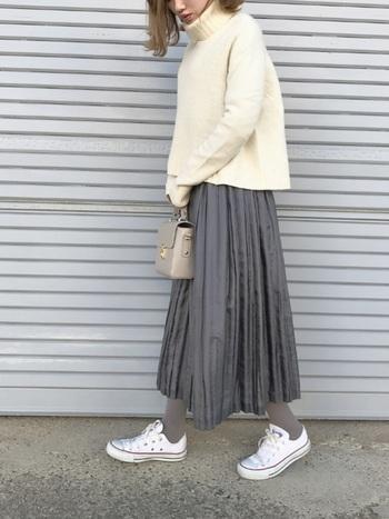 白のタートルネックに合わせたのは、動くたびにふわりと揺れるグレーのプリーツスカート。絶妙な丈感でスニーカーはもちろん、ショートブーツやパンプス+靴下の組み合わせも楽しみたいアイテムです。足元をスニーカーでカジュアルに着崩したら、きちんと感のある小さめのレザーバッグで今年らしい印象に仕上げて。